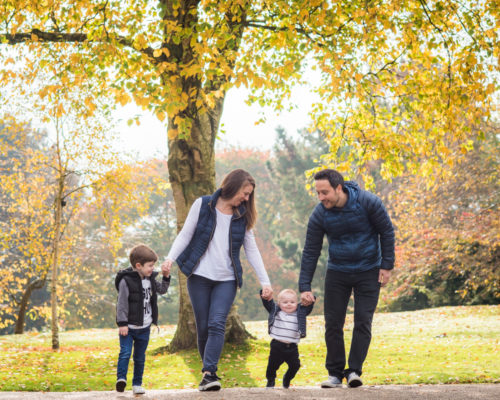Walking family in Autumn leaves