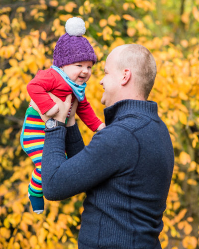 Flying baby with Dad in the woods in Autumn