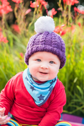 Jake smiling in his bobble hat for his baby photos