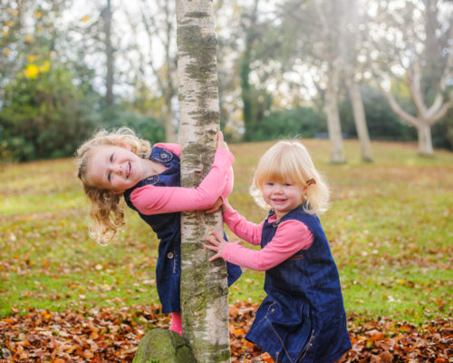 Sisters peeping around tree in Autumn
