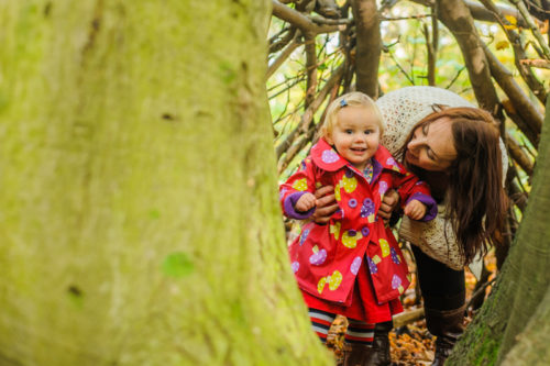 Peeping mum and girl in woods for photo session in Lake District