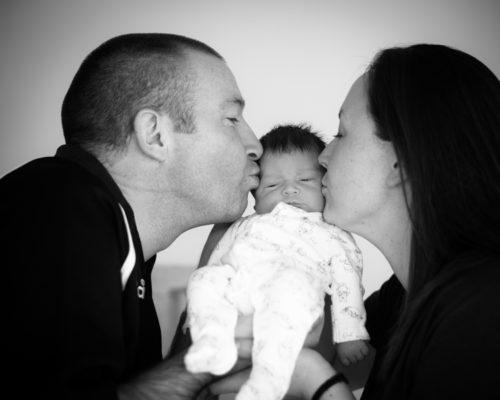 Mum & Dad kissing newborn Abby in photo shoot in Cockermouth