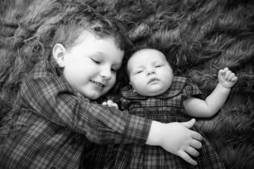 Cuddles for his little sister - newborn photographers Cumbria