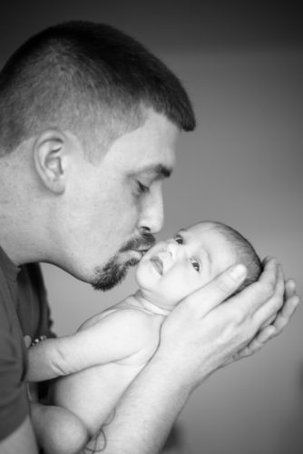 Dad kissing baby, newborn photographers Cumbria