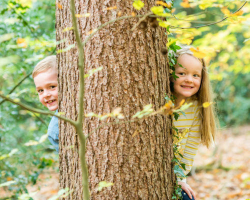 Siblings peeping around tree, Cockermouth baby photographers