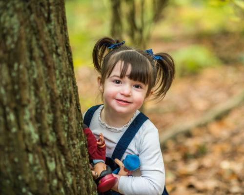 Penny peeping around tree, baby photographer Cockermouth