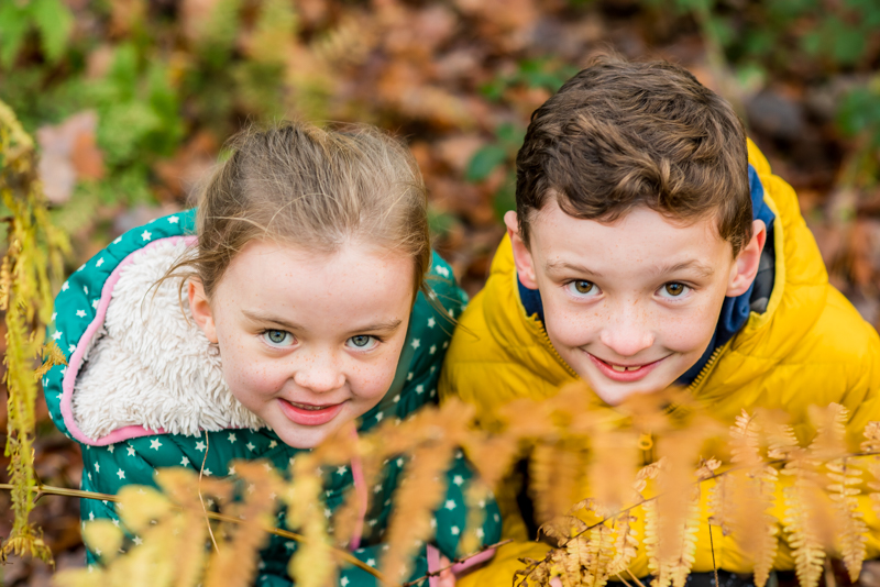 Brother and sister peeping through ferns, Cockermouth baby photographers