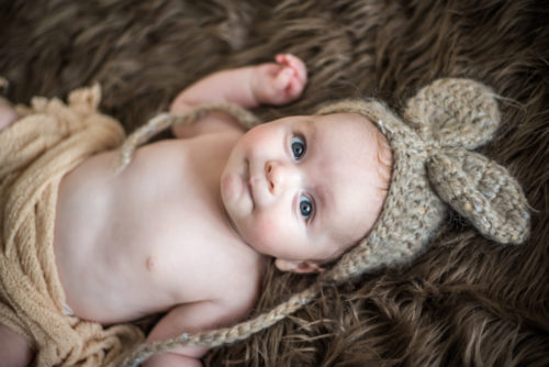 Cheeky Henry in rabbit hat, newborn photographers Keswick