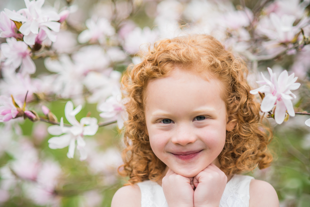 Smiling in front of blossom tree, baby photographers Cumbria