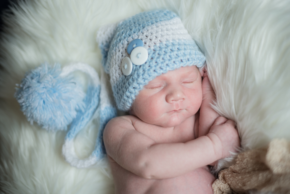 Cuddled up baby in hat, newborn portraits Cumbria