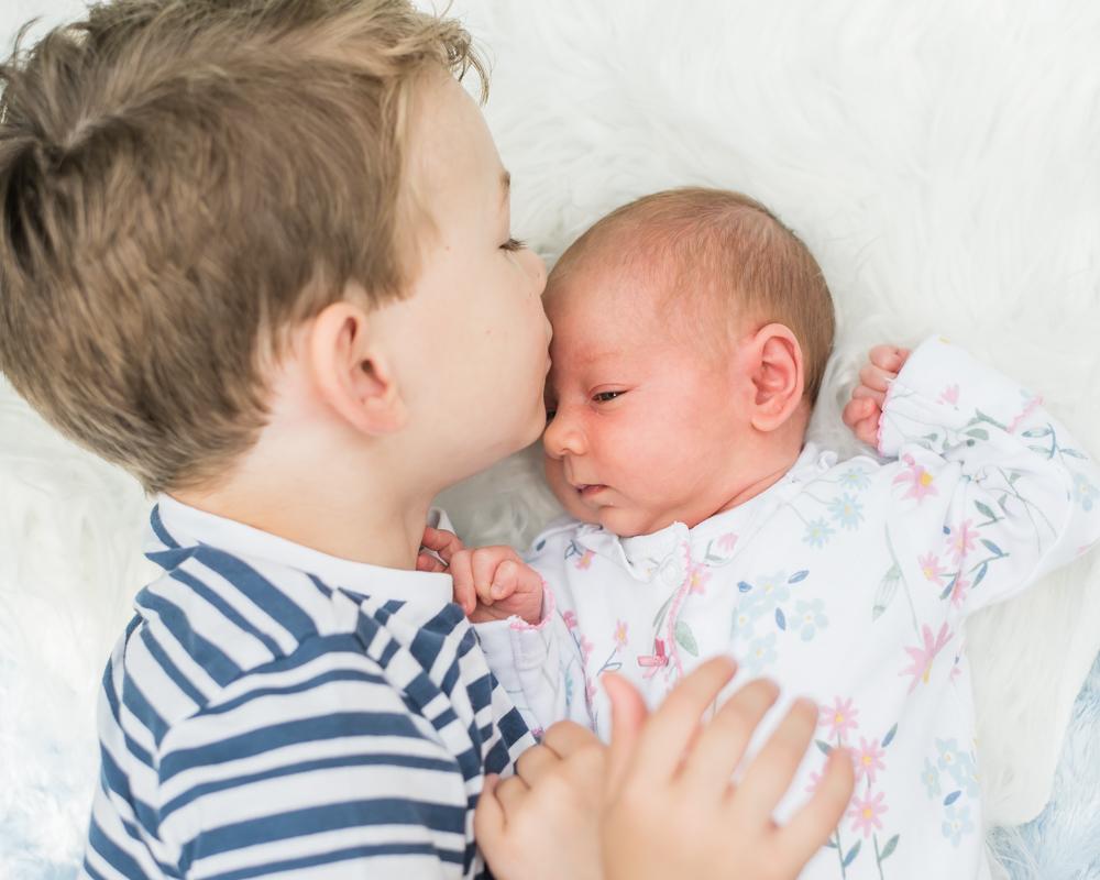 Jacob kissing his sister Delphie, family portraits Wigton newborn photographers