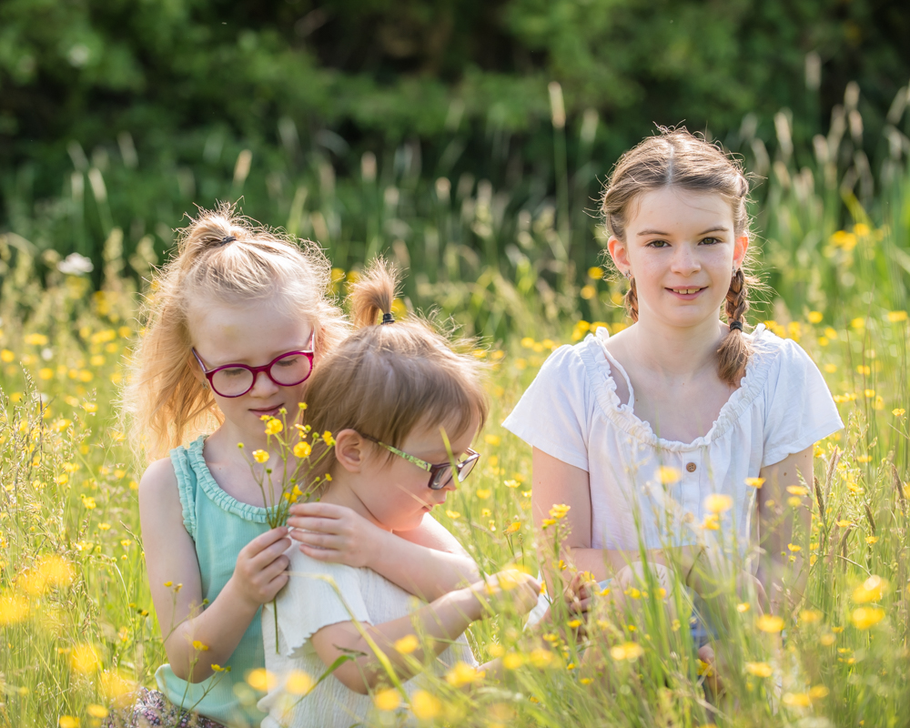 Sisters crouching in field with buttercups, baby photographers Wigton