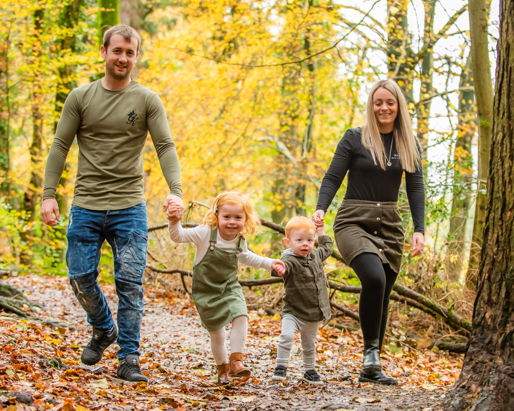 Family walking together through Autumn trees in Dodd Wood in the Lake District