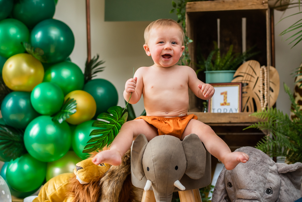 Smiling for camera in safari theme first birthday photoshoot